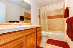 Banheiro morno das cores com toalhas e o tapete vermelhos Fotografia de Stock Royalty Free