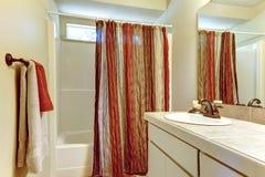 Banheiro simples com cores do vermelho e dos marrons na cortina de chuveiro e Foto de Stock