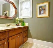 Banheiro verde simples clássico com gabinetes de madeira. Fotografia de Stock