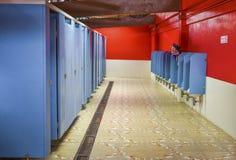 Banheiro vermelho da parede com um mictório para homens Imagens de Stock