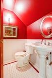 Banheiro vermelho e branco com suporte e toalete da bacia Imagem de Stock
