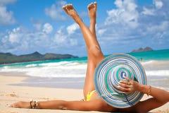 Banho de sol bonito da mulher em uma praia Fotografia de Stock