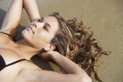 Banho de sol bonito da mulher na praia Foto de Stock