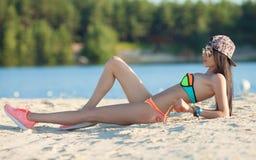 Banho de sol bonito de sorriso da mulher em uma praia Foco na menina Fotografia de Stock Royalty Free