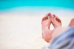 Banho de sol da jovem mulher na praia branca pés Fotos de Stock