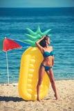 Banho de sol da menina na praia com colchão de ar menina no roupa de banho na praia ensolarada fotos de stock