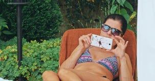 Banho de sol da mulher na cadeira pela associação filme
