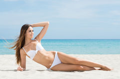 Banho de sol da mulher na praia Fotografia de Stock Royalty Free