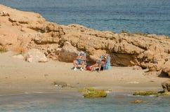Banho de sol dos pares em uma praia fotografia de stock royalty free