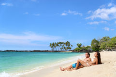Banho de sol dos pares no abrandamento das férias da praia fotos de stock royalty free