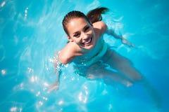 Banho de sol e natação bonitos exóticos da mulher foto de stock