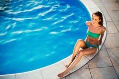 Banho de sol e natação bonitos exóticos da mulher imagem de stock