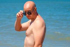 Banho de sol feliz do homem que está pelo conceito do feriado do mar imagem de stock