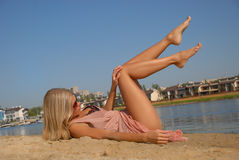 Banho de sol louro bonito novo da mulher no beira-mar Fotografia de Stock Royalty Free