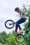 Banhoppning för cyklist för BMX-fristil tonårs- i luft Arkivfoto