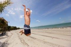 Banhoppning för hög man på stranden arkivfoto