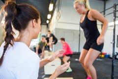 Banhoppning för instruktörEncouraging Athlete In ask Arkivbilder