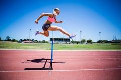 Banhoppning för kvinnlig idrottsman nen ovanför häcken Arkivfoto