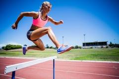 Banhoppning för kvinnlig idrottsman nen ovanför häcken Royaltyfria Foton