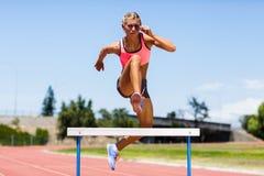 Banhoppning för kvinnlig idrottsman nen ovanför häcken Fotografering för Bildbyråer