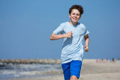 Banhoppning för tonårs- pojke som kör på stranden Arkivbild