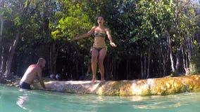 Banhoppning för ung kvinna in i Emerald Pool Pond med blått vatten Extrem aktivitet Gopro HD för ultrarapid thailand lager videofilmer