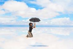Banhoppning för ung kvinna med paraplyet Arkivbilder
