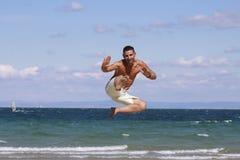 Banhoppning för ung man mot blå himmel och havet. Royaltyfria Bilder