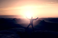 Banhoppningfotvandraren i svart firar triumf mellan två steniga maxima Underbar gryning med solen ovanför huvudet Arkivfoton