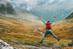 Banhoppningmannen med ryggsäcken räcker lyftt berglandskap arkivfoto