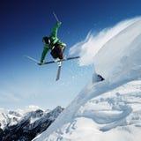 Banhoppningskidåkare i höga berg på skida arkivfoto