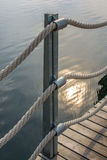 Banister with thick ropes over calm water Royalty Free Stock Image