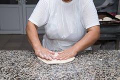 Κλείστε επάνω των θηλυκών χεριών που ζυμώνουν τη ζύμη και που κάνουν το banitsa Στοκ Φωτογραφία