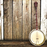 A Banjo leaning on a wooden fence. Advertisement with room for text or copy space Stock Photography