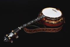 Banjo metálico aislado en fondo negro Fotos de archivo