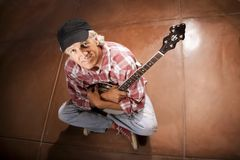 Banjo Player Sitting on Cement Stock Photography