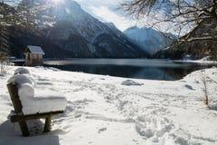 Bank abgedeckt mit schneebedeckter Decke durch szenischen Gebirgspass lake Lago Del Predil in der Winterlandschaft, Italien Stockfotos