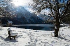 Bank abgedeckt mit schneebedeckter Decke durch szenischen Gebirgspass lake Lago Del Predil in der Winterlandschaft, Italien Lizenzfreie Stockbilder