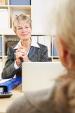 Bank adviser listening to senior Royalty Free Stock Photos