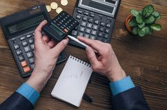 Bank adviser. Tax inspector. Manager whith calculator. Tax inspector or banker desk table background. Businessman male hands, notepad and calculator on wooden Stock Images