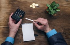 Bank adviser. Tax inspector. Manager whith calculator. Tax inspector or banker desk table background. Businessman male hands, notepad and calculator on wooden Royalty Free Stock Photos