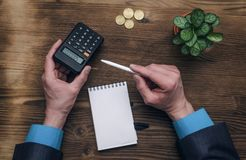 Bank adviser. Tax inspector. Manager whith calculator. Tax inspector or banker desk table background. Businessman male hands, notepad and calculator on wooden Royalty Free Stock Images