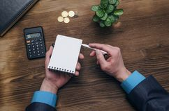 Bank adviser. Tax inspector. Manager whith calculator. Tax inspector or banker desk table background. Businessman male hands, notepad and calculator on wooden Royalty Free Stock Photo