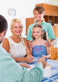 Bank agent consulting family with kids. At a home interior Royalty Free Stock Photo