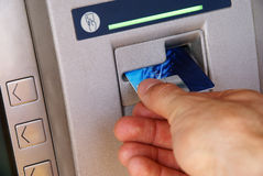Bank ATM machine. Inserting credit card into dispenser to withdraw money