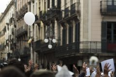 Bank balloon during a protest through the streets. A bank balloon rises over the raised hands of people who demonstrate during a protest in the streets stock image