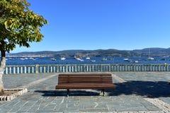 Bank, Baum und Steinhandlauf in einer Strandpromenade Blaues Meer, Himmel u Bucht mit blauem Wasser, Booten und Bäumen Galizien,  stockfotografie