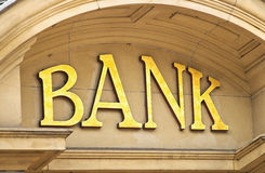 Bank building sign. Gold Bank sign at the entrance to a Banking institute in the centre of the financial sector stock photography