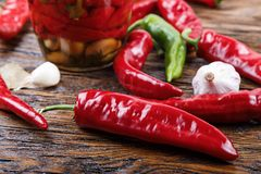Red and green chili peppers with spices are lying on the table. Bank of canned chili peppers, lies next to the garlic, bay leaf, olive oil and raw hot peppers Stock Photos