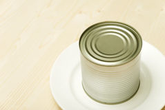 Bank of canned food on a white plate Stock Photos